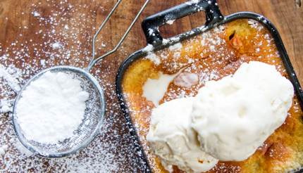 Malva pudding with vanilla ice cream on top and icing sugar on the side