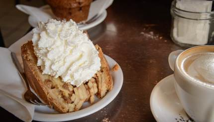 Apple pie (appeltaart) with whipped cream on top and a coffee on the side