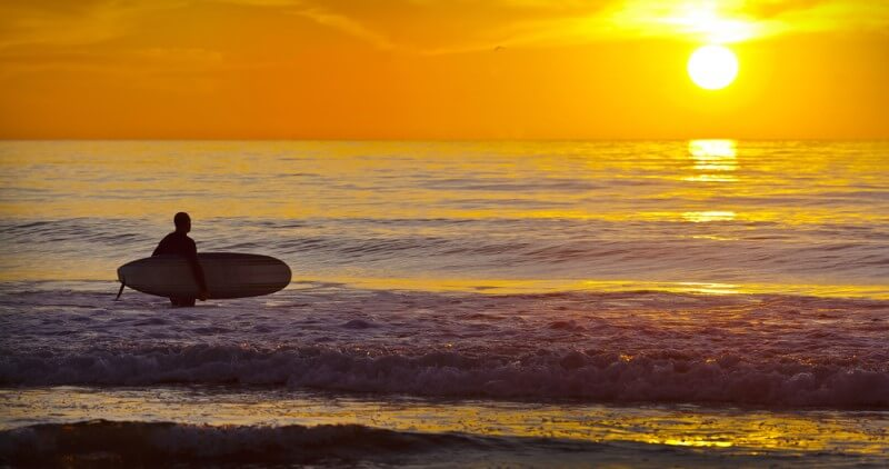 A man with his surfboard looking at the San Diego sunset while standing in the ocean