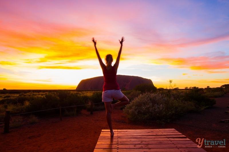 Yoga during sunrise at Uluru in Central Australia