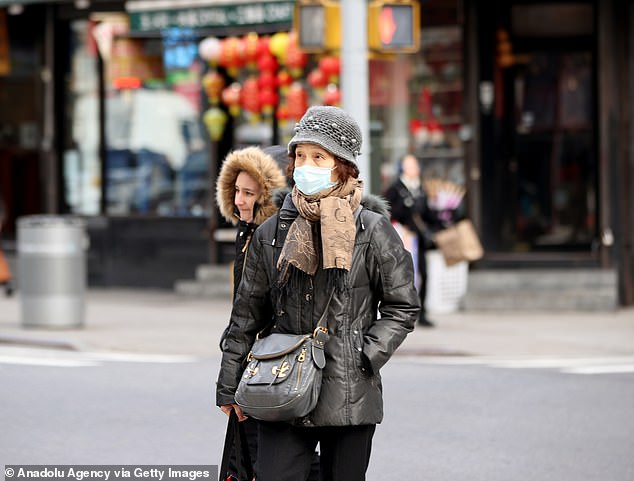 Serious issue: People wear medical masks as a precaution against infection, walking around the streets of New York City on Thursday. The World Health Organization declared coronavirus a public health emergency of international concern
