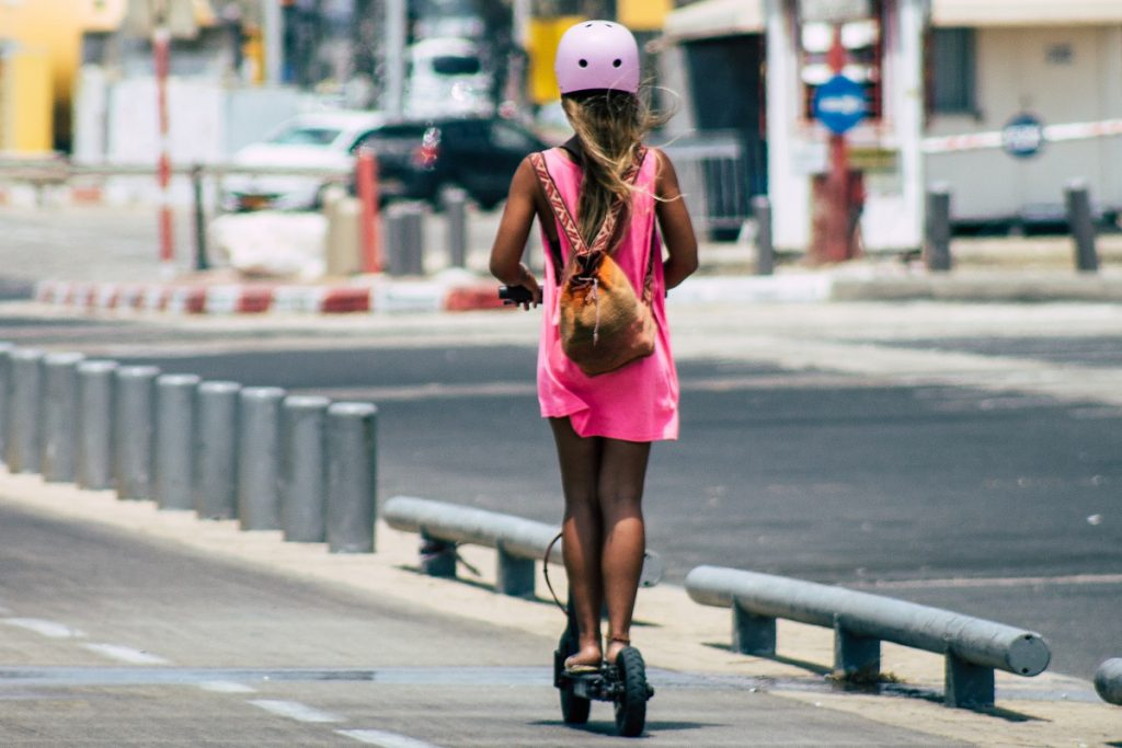 A girl rides her electric scooter on an afternoon in Tel Aviv. Deposit Photos