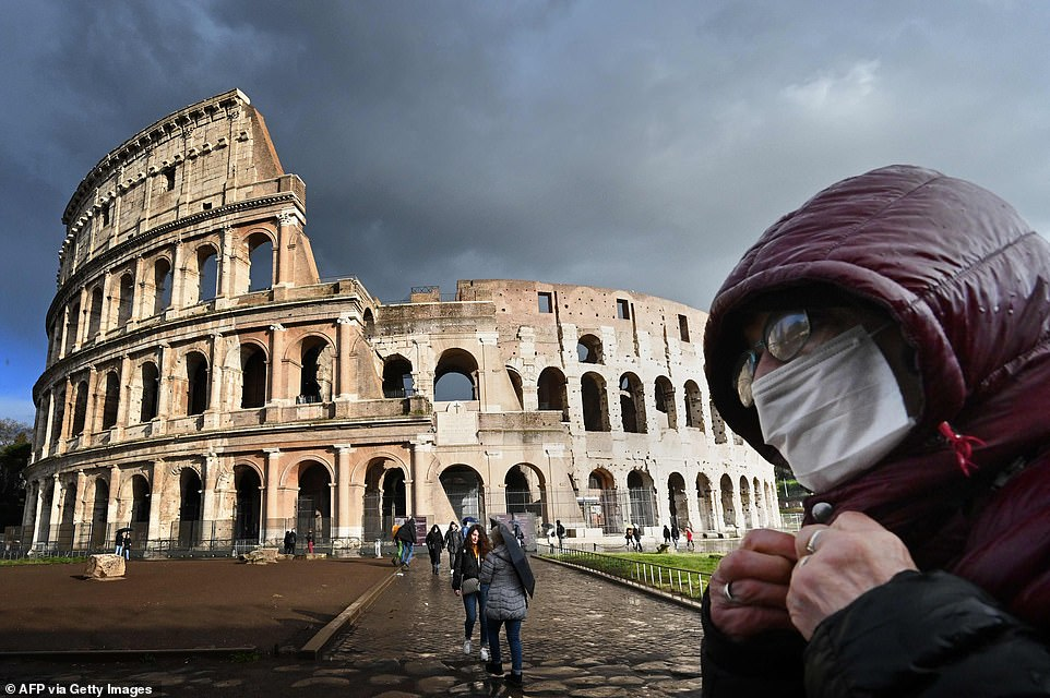 A man wearing a protective mask passes by the Coliseum in Rome today amid fears of the  Covid-19 epidemic