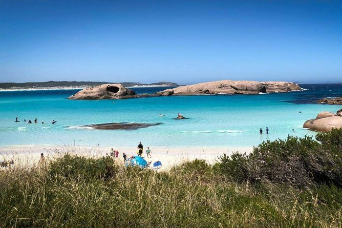 Bright blue waters and white sands of a beach in south-west WA with people on beach and in water and rocks in water
