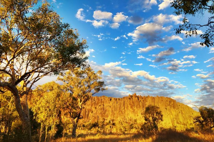 Blue sky mottled with small white clouds and below the Kimberley natural monument of Windjana Gorge surrounded by trees