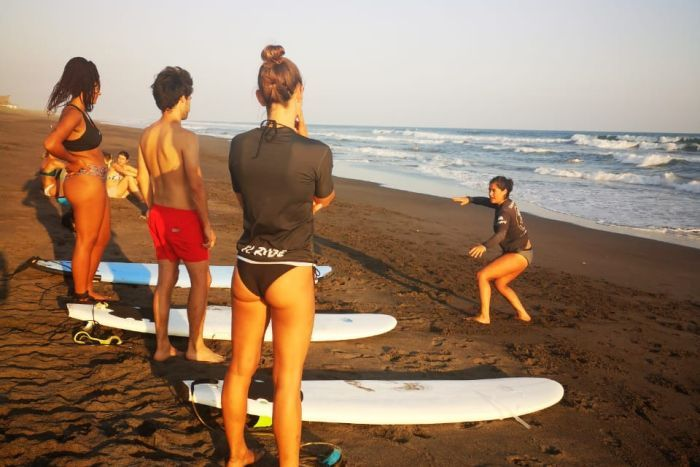 A group of people take a surfing lesson on the beach, in el Paredon, Guatemala.