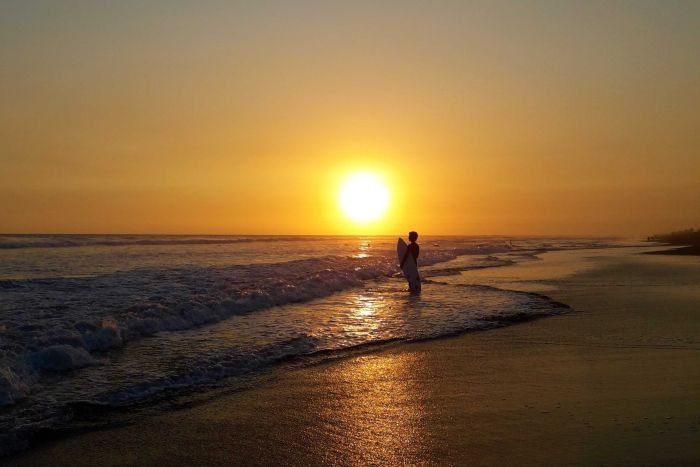 A surfer eyes the break at sunset at Playa el Paredon, Guatemala.