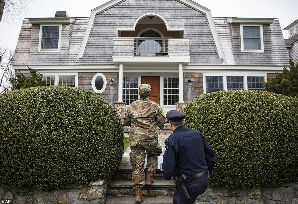 A member of the Rhode Island National Guard approaches a property to check for New Yorkers on Saturday after the state ordered mandatory quarantine for people visiting from the hard-hit state