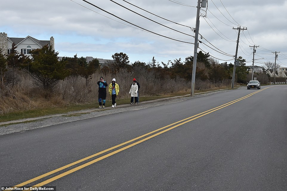 A group of people stretch their legs by taking a walk along Dune Road in Quogue on Tuesday