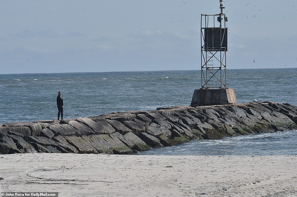 A man looks out at the ocean at Shinnecock Inlet on Tuesday