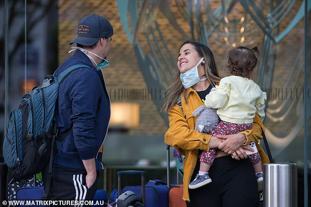 People are seen leaving Melbourne's Crown Promenade hotel on Sunday after two weeks in quarantine (pictured) having returned to Australia from overseas