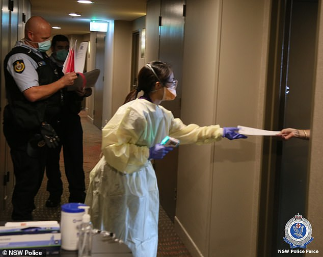 Travellers are seen being given daily information packs inside a Sydney hotel where returning Australians are doing their 14 days in isolation (pictured)