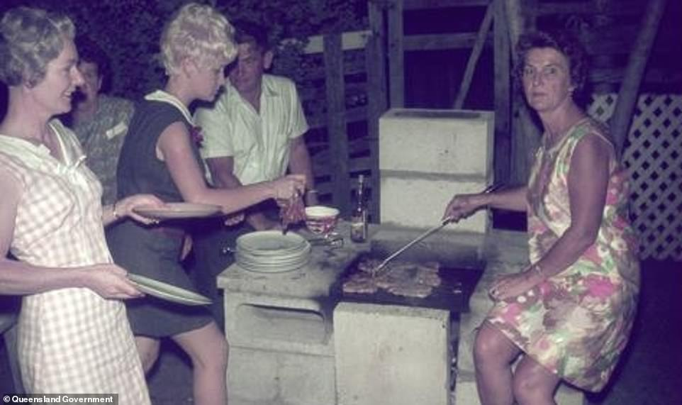 Women are seen cooking over a BBQ in Queensland in 1970 (pictured). The 70s was the golden age of dinner parties, with friends regularly bringing dishes to their neighbours' homes