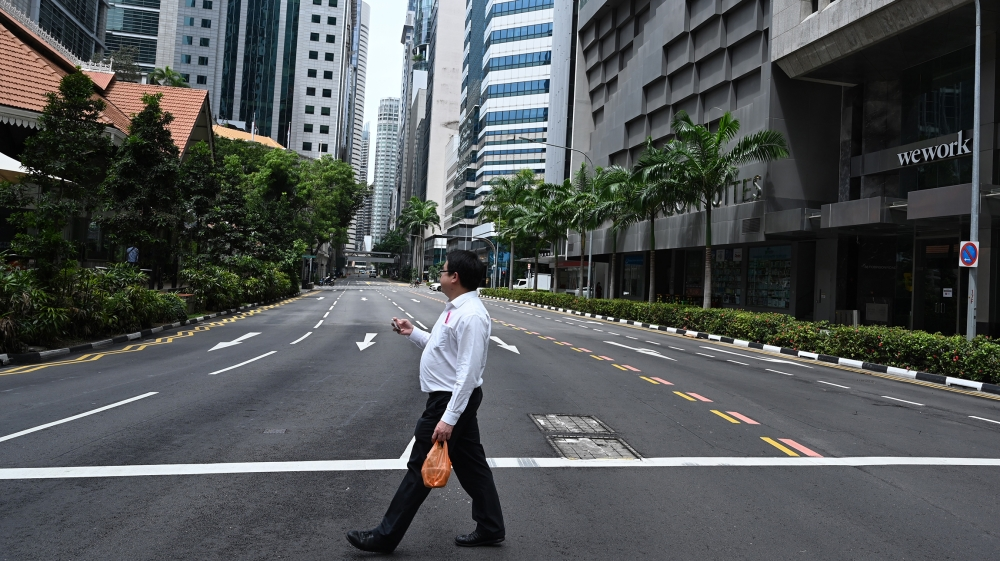 A man crosses an empty street in the central business district of Singapore on April 7, 2020, as the country ordered the closure of all businesses deemed non-essential as well as schools to combat the