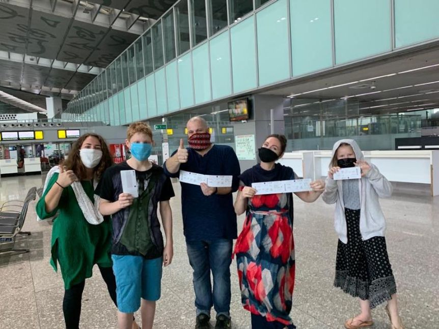 Two women, a man and two kids wearing masks hold tickets up to the camera as they wait at an airport.