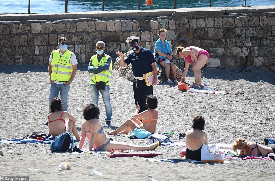 A police officer talking to beach-goers in Italy. The UK has more cases of coronavirus per million people than most of the 15 most popular holiday destinations for Britons - including Italy