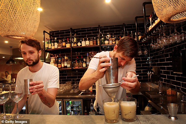 Bar tenders are seen preparing cocktails for punters in Sydney's Newtown on Friday night (pictured)