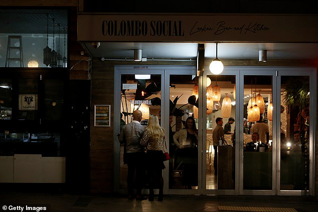 Couples are seen queuing outside Colombo Social in Sydney on Friday night (pictured) as residents hit the town with coronavirus restrictions eased