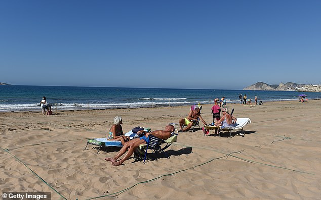 Belgium tourists sunbathe in a roped off area at Levante beach, Benidorm after the town's beaches were reopened after three months of closure on June 15