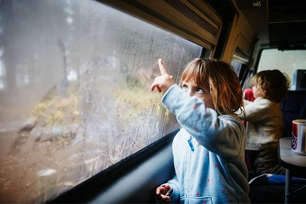 Children drawing on windows inside camper van