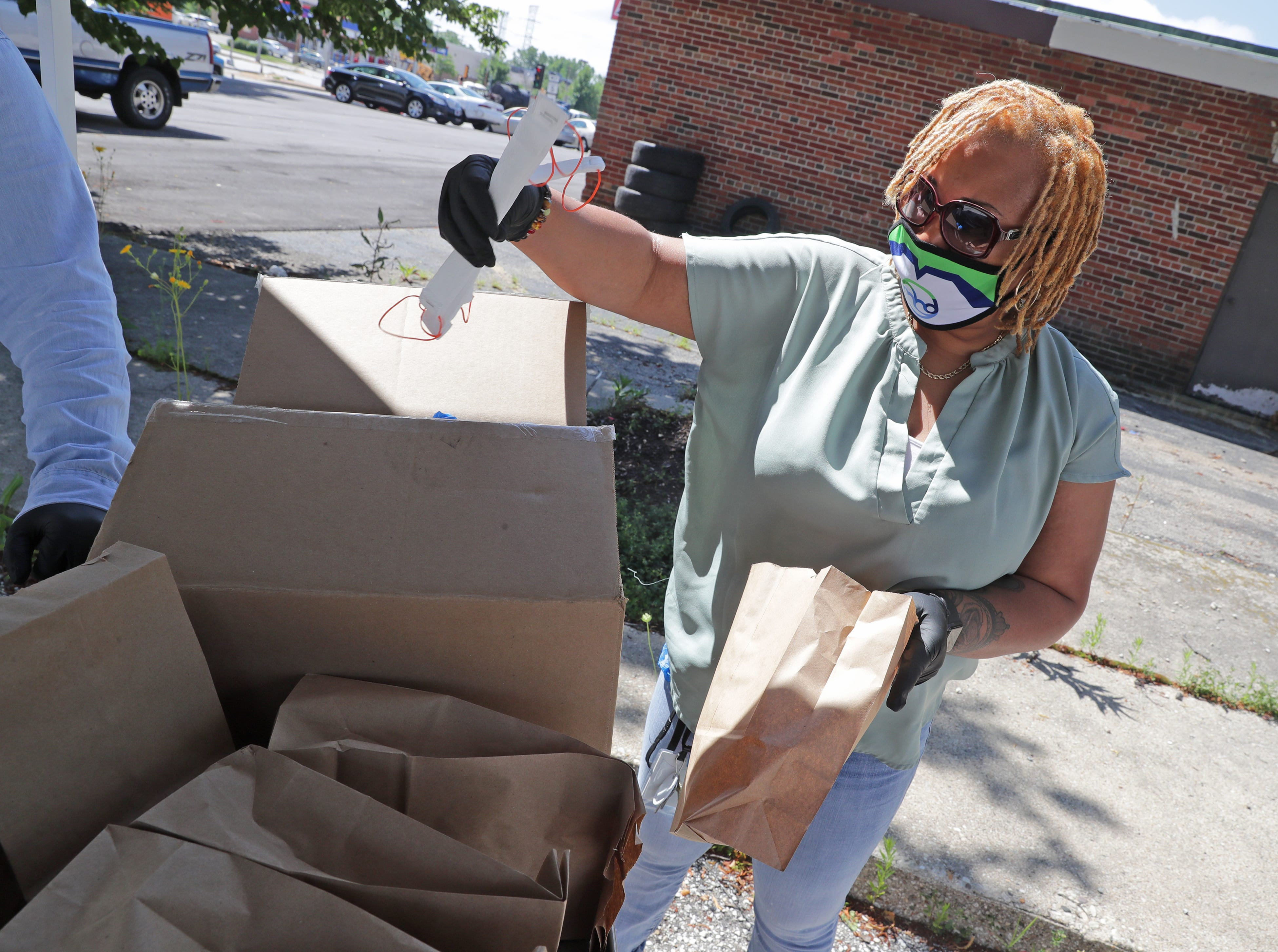 Erica Swan, with the Milwaukee Health Department, prepares bags with face masks before handing them out at the City Of Milwaukee Health Department-Northwest Health Center at 7630 W. Mill Road Milwaukee on July 16.