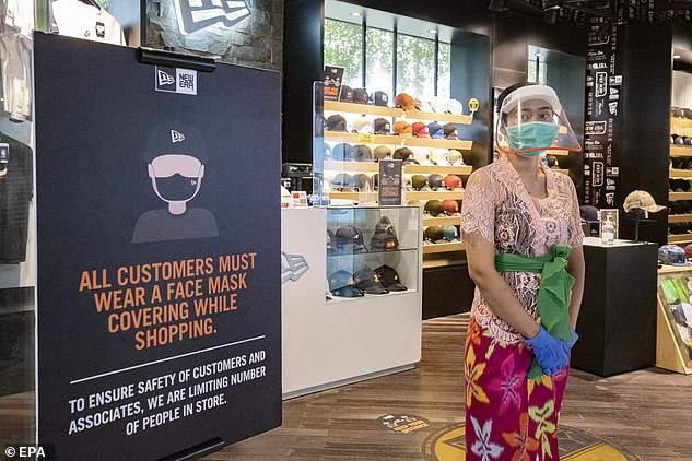A woman wears a protective face mask at a shopping mall in Bali. Plans to reopen the island to foreign tourists have been shelved to at least the end of the year
