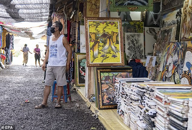 A shop keeper waits for customers at a market in Gianyar, Bali on August 20.Face masks are mandatory in public across Indonesia