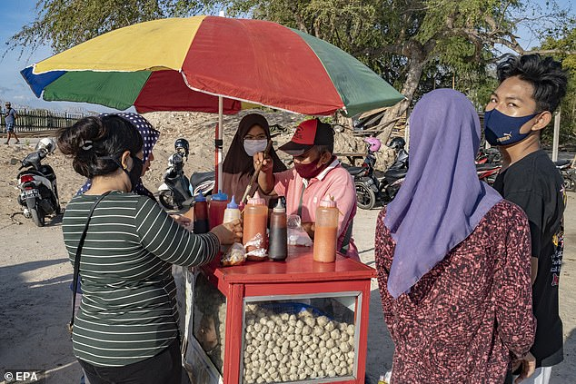 Local epidemiologist Dr I Gusti Ngurah Kade Mahardika said reopening the island to tourists was to blame (Pictured: A street food vendor and customers wear face masks in Bali, Indonesia)