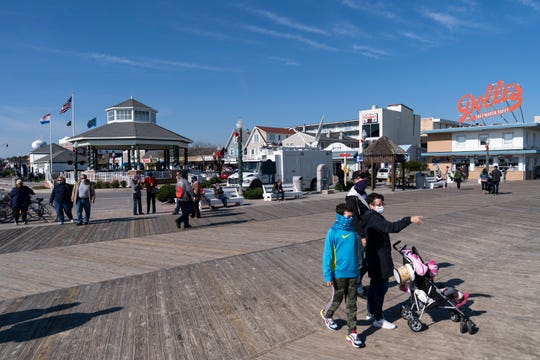 """People enjoy the boardwalk, Friday, Nov. 13, 2020, in Rehoboth Beach, Del. This resort town known for Atlantic waves that are sometimes surfable, fresh-cut French fries and a 1-mile wooden boardwalk that dates back to the 1870s has long prided itself on being the """"Nation's Summer Capital."""""""