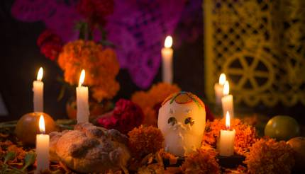 Sugar skull with candles, bread and flowers decoration