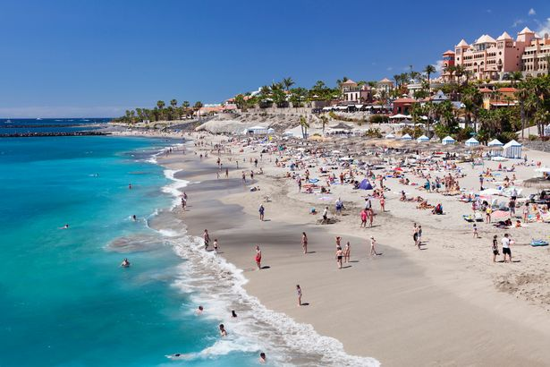 Tourists enjoy the sunshine at Playa del Duque beach in Tenerife